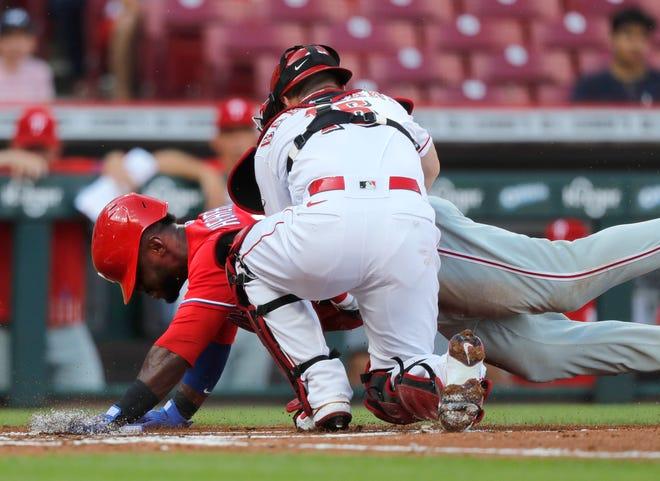 Jun 28, 2021; Cincinnati, Ohio, USA; Philadelphia Phillies center fielder Odubel Herrera (37) is tagged out at home by Cincinnati Reds catcher Tucker Barnhart (16) during the first inning at Great American Ball Park.