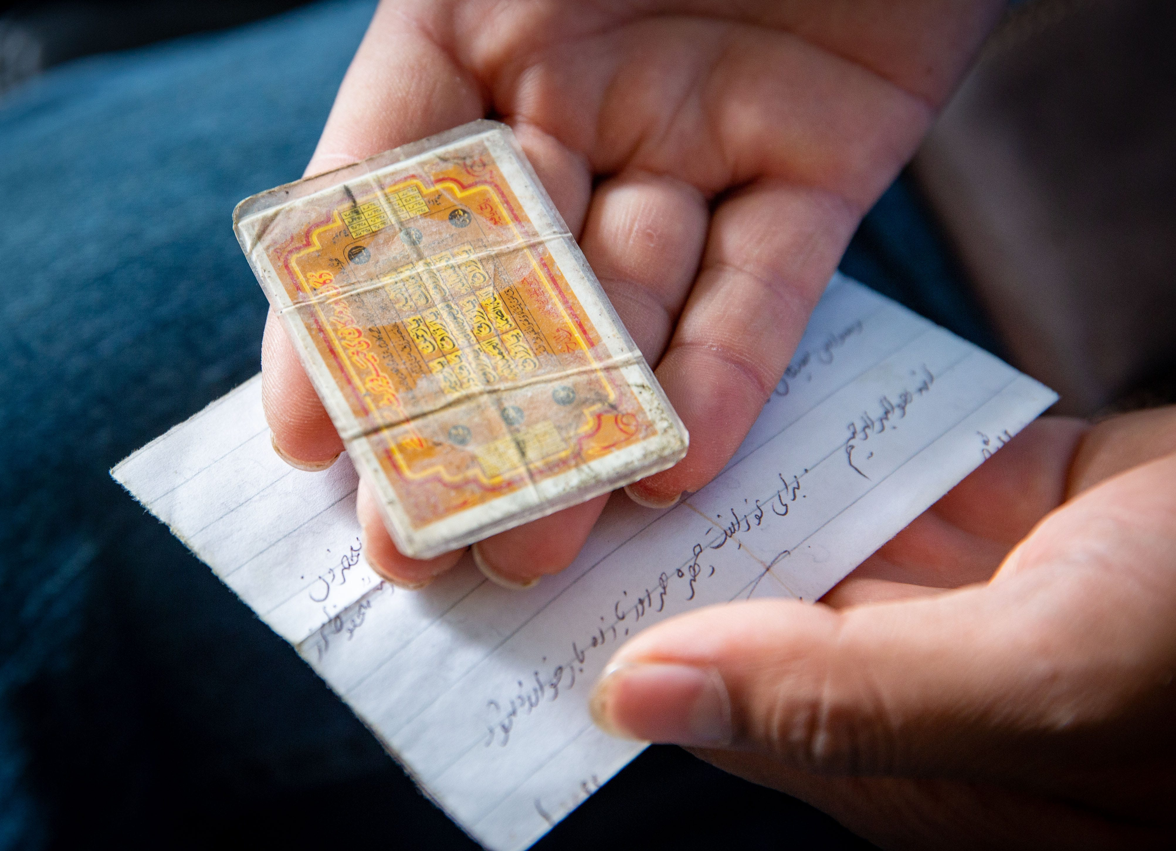 Zalmay Niazy holds a prayer card his father gave him while he was working as a translator for U.S. troops.