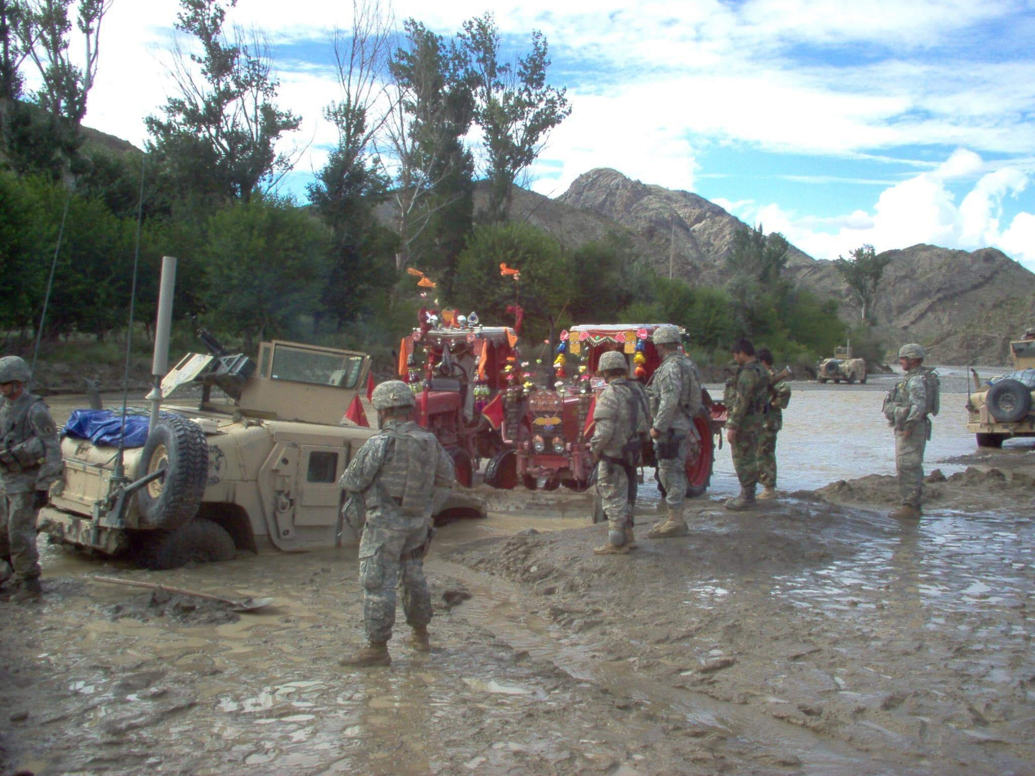 """In 2007, Zalmay Niazy became part of an """"embedded training team"""" to help U.S. forces mentor Afghan soldiers. Here he helps troops navigate a flooded road."""
