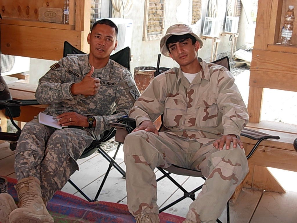 Zalmay Niazy, right, poses with one of his superiors while working as an interpreter with U.S. forces in his native Afghanistan.