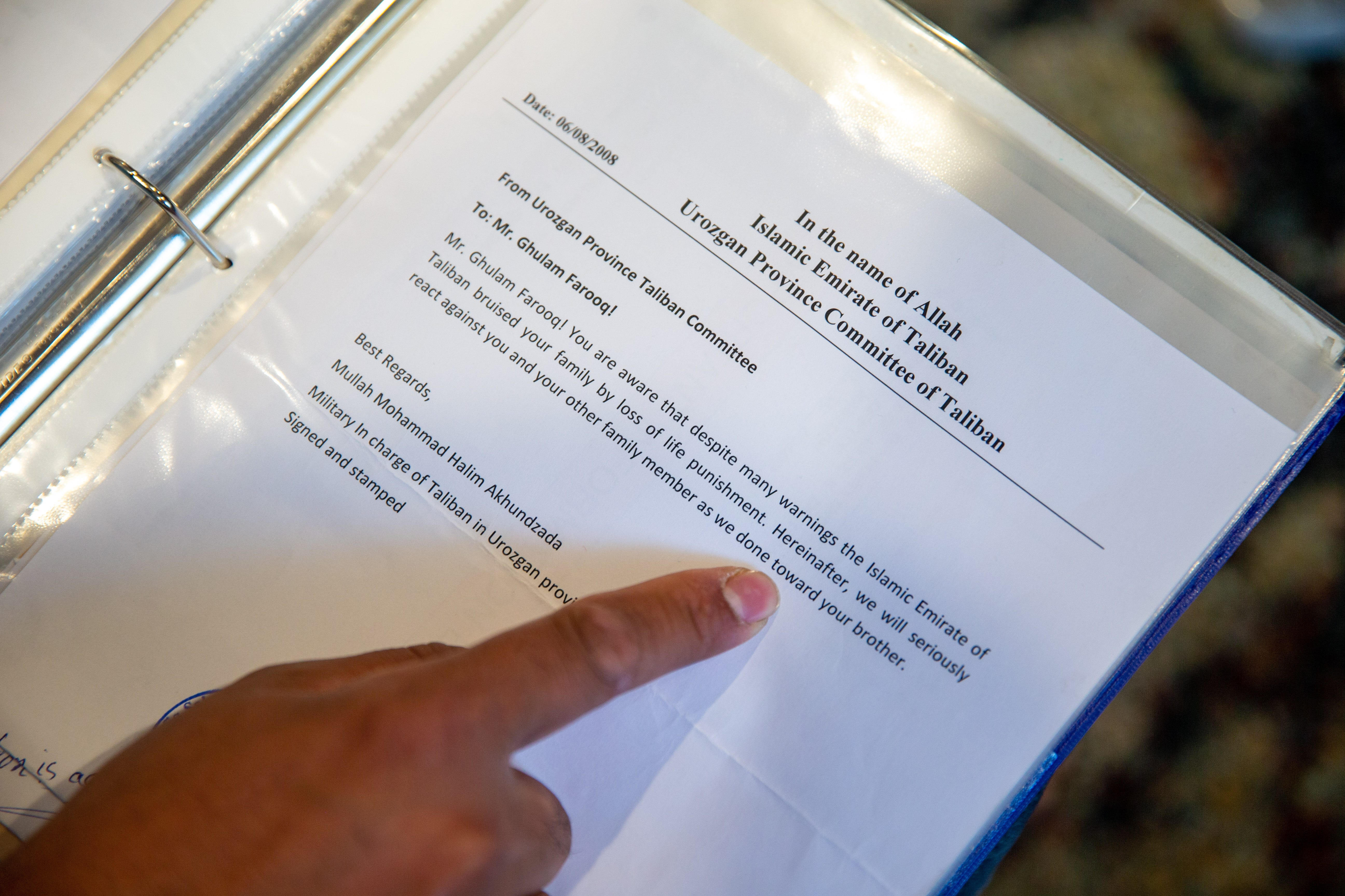 Zalmay Niazy looks over a binder with threat letters he received from the Taliban while he was working for the U.S. government.