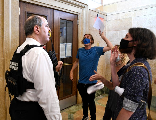 Tom Conley, president and CEO of the private security firm The Conley Group, argues with John Noble, 26, as Noble demands to know why he and others were being denied access to a Des Moines City Council meeting on June 28.