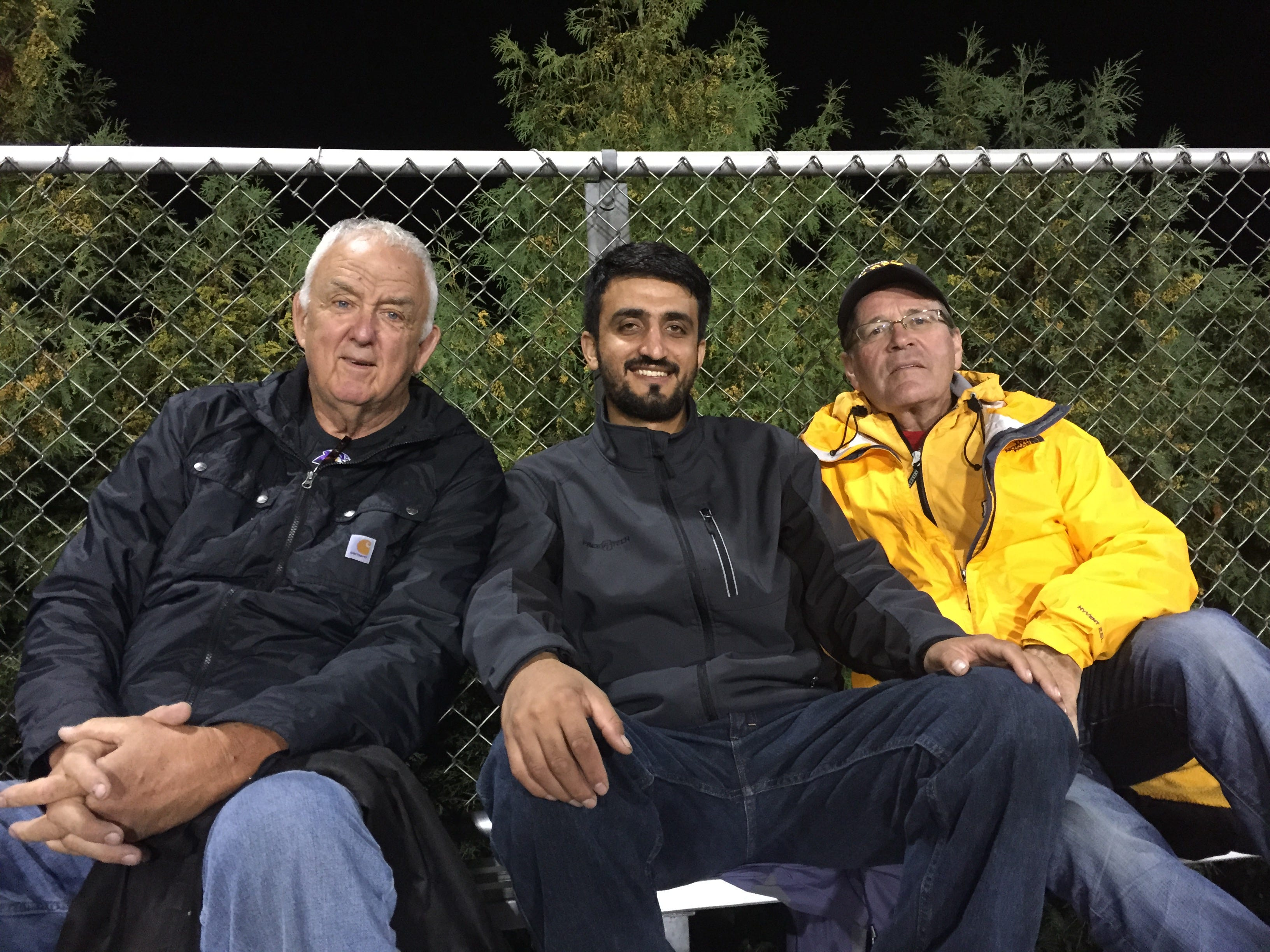Zalmay Niazy, center, takes in a high school football game in Iowa Falls. Friend and confidant, Mike Ingebritson, sits to his left.