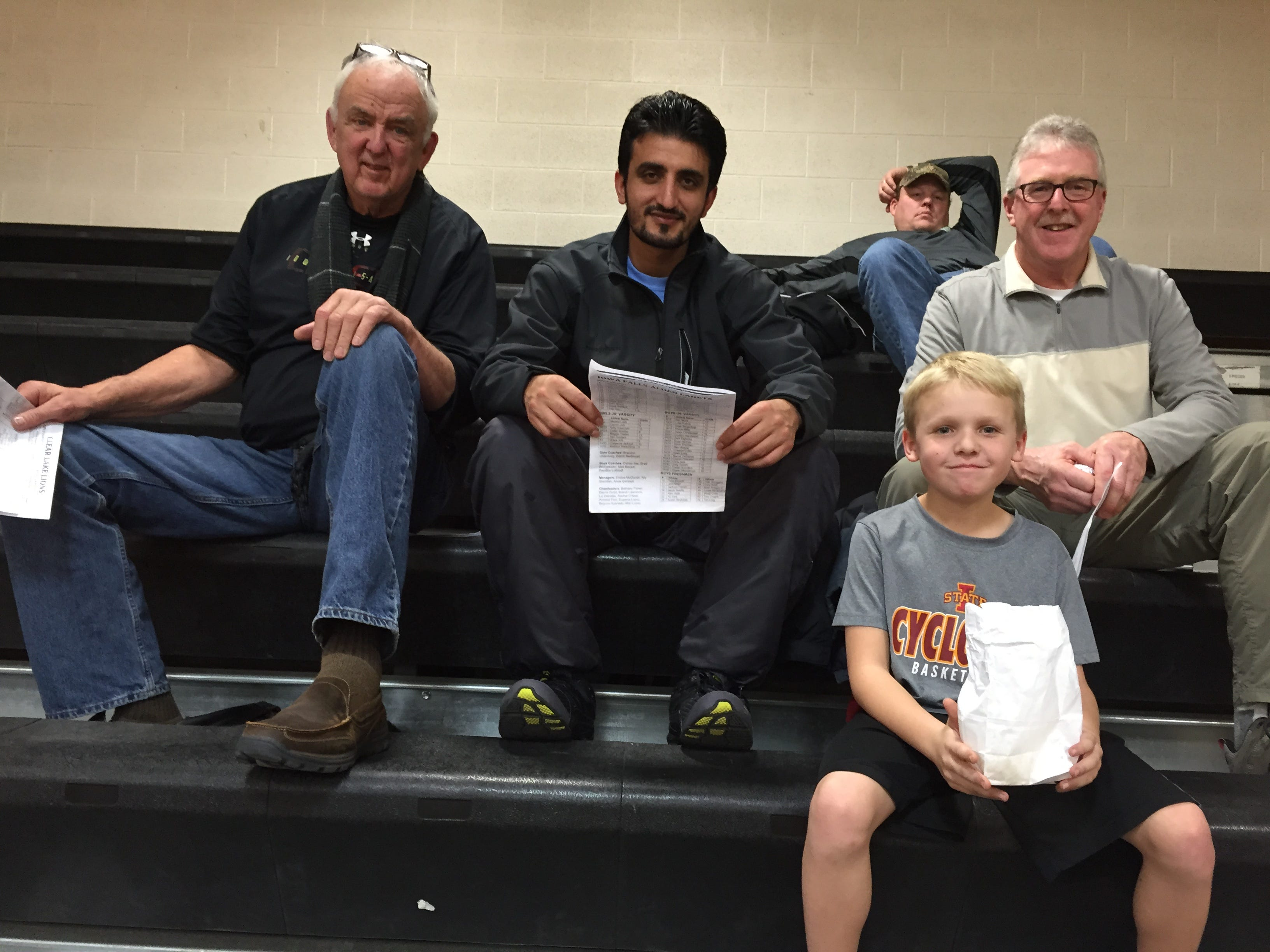 Zalmay Niazy, center, takes in a high school basketball game in Iowa Falls. Friend and confidant, Mike Ingebritson, sits to his left.