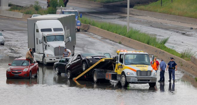 As the floodwaters starting to go down on East and West I-94, tow trucks started arriving to remove stuck and stalled cars near Trumbull in Detroit on June 26, 2021. Heavy rains in Metro Detroit caused massive flooding in homes, streets and freeways.