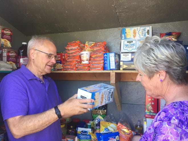 Lexington Mayor Brian White hands off a box of saltines to Cathy McGlone at the new Lexington Area Little Food Pantry.