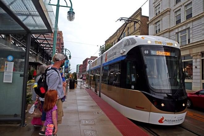 """Greg Flattery prepares to board a Hop streetcar with children Maeve, 5, and Ronan, 2, on East St. Paul Avenue on Thursday, June 24, 2021. The Hop will return to its regular schedule and frequency starting August 1 and will host """"Hop Summer Nights"""" every Sunday of the month."""