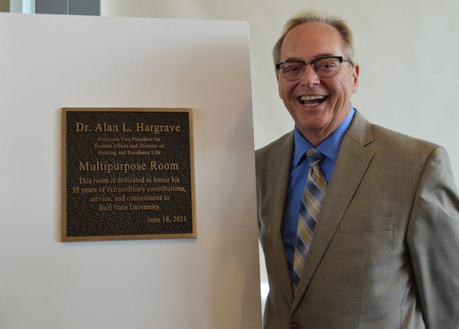 Alan L. Hargrave poses with a plaque naming the Park Residence Hall Multipurpose Room after him shortly before his recent retirement as associate vice president of student affairs and director of housing and residence life at Ball State University.