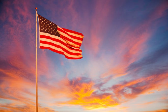 An orange and pink sunset surround the American Flag and makes it glow with pride.