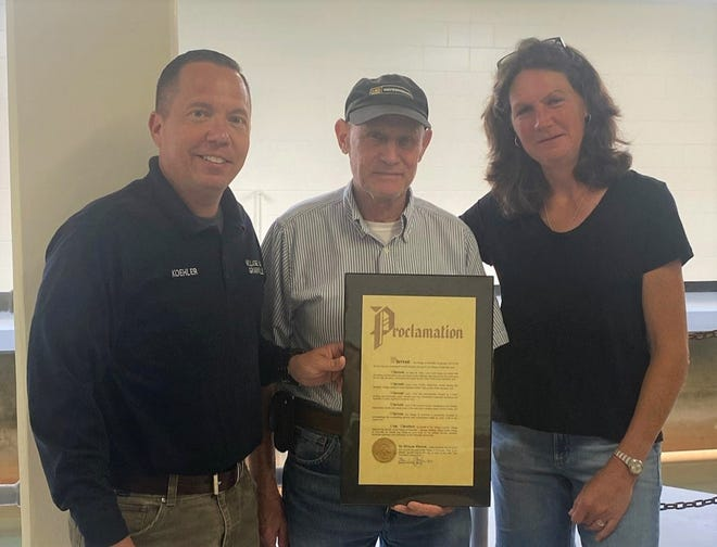 Larry Fruth accepts his award for service from Granville Village Manager Herb Koehler (left) and Mayor Melissa Hartfield (right).