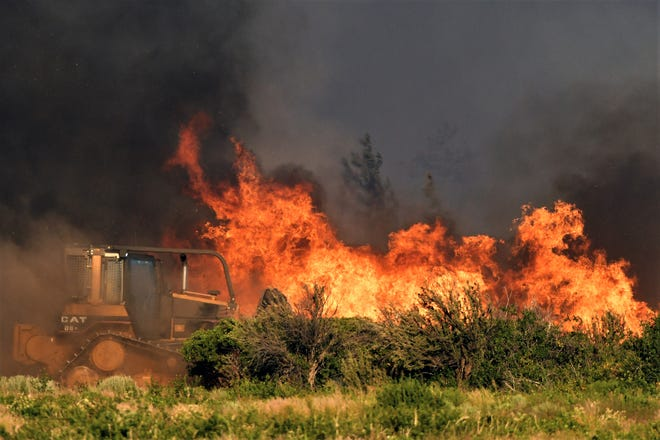 A bulldozer operator works on a fire line as vegetation burns nearby at the Lava Fire on Monday, June 28, 2021, north of Weed.  Officers shot and killed a man who pulled a gun as they tried to keep him out of a complex of marijuana farms in an area of far Northern California where thousands of people have been ordered to evacuate because of the raging wildfire.