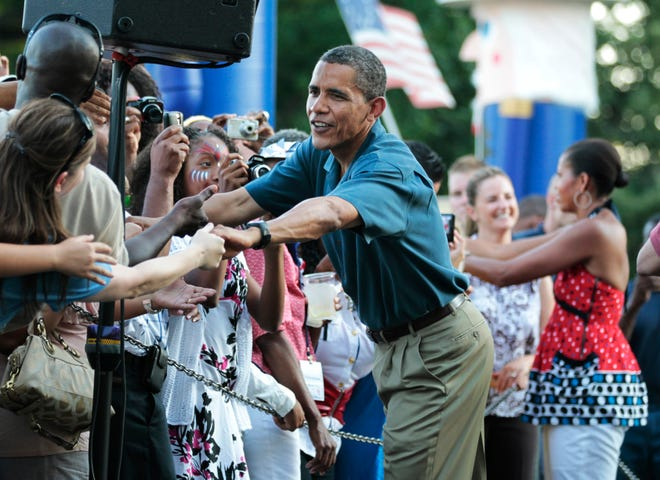 President Barack Obama and first lady Michelle Obama greet members of the U.S. military and their families as they host an Independence Day celebration on the White House's South Lawn on July 4, 2010.