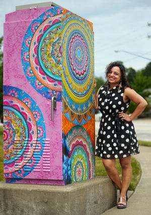 Artist Nirali Schrader shows the utility box she designed for the city of Stow at the corner of Graham and Fishcreek roads.