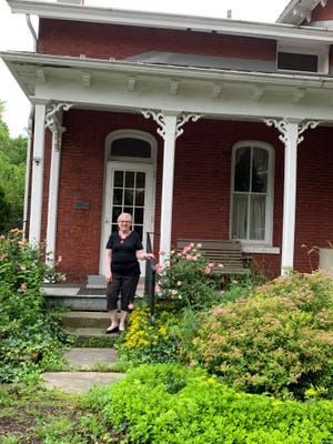Betty Jo Blevins, standing on the steps of Mabel Hartzell Historic Home in Alliance, was part of a Jane Bain DAR group tour of the site.