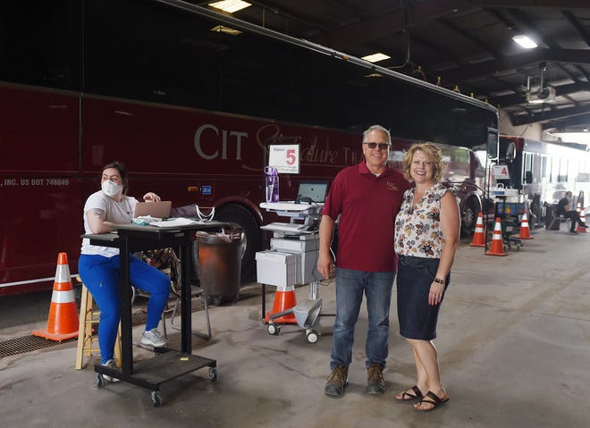 CIT Signature Transportation services owners Kim and John Grzywacz pose in the Story County COVID-19 testing center at their transportation facility Tuesday, June 29, 2021, in Ames, Iowa.