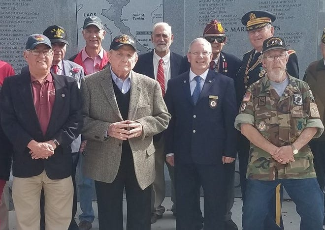 Vietnam veteran Bobby Hawes (second from left) stands at the downtown Augusta Vietnam Memorial, which he helped establish. He will lower the U.S. flag at the Normandy American Cemetery in September.