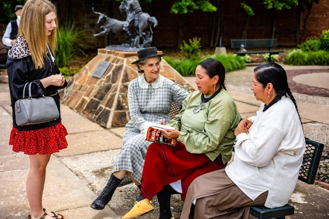 """Emily Burton asks movie extras Rebecca Renfro, Chay Nicholas and Lisa Yates to sign her grandfather's copy of """"Killers of the Flower Moon"""" as a surprise gift for him during a day of filming director Martin Scorsese's film adaptation of the book in Pawhuska."""