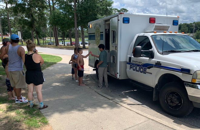 """Children and families line up for free popsicles as the Crestview Police Department's """"Copsicle Cruiser"""" pops up in Twin Hills Park recently."""