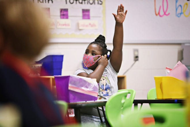 FILE - In this Oct. 26, 2020 file photo, Ariel Williams raises her hand to answer a question in her first-grade class where students work from spaced tables at Hunter Elementary School in Raleigh, N.C., on the first day back in school for some Wake students. A report released on Wednesday, June 30, 2021, found that about 1 in 3,000 middle and high school students who attended classes under the loosest reopening guidelines became infected with COVID-19 due to in-school transmission. The findings from Duke University and the University of North Carolina School of Medicine show that mask wearing is the best way to reduce COVID-19 transmission.  (Juli Leonard/The News & Observer via AP, File)