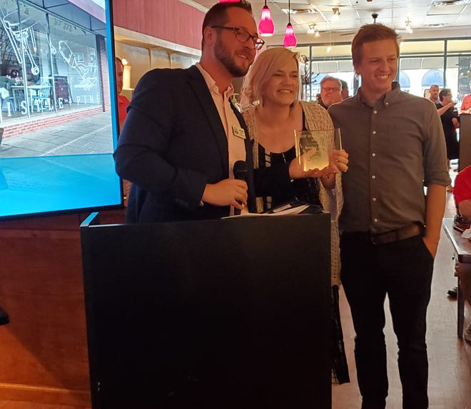 Bristle + Pine owners Bobbie (center) and Bradley Key (right) receive the 2021 Uptown Lexington Inc. New Business of the Year Award from ULI Executive Director Jacob Gordon (left) Tuesday evening.