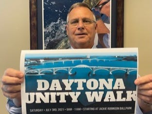 Daytona Unity Walk organizer Brooks Tomblin holds a flier promoting the free community event set for Saturday, July 3, 2021, from 9 to 11 a.m. at Jackie Robinson Ballpark in Daytona Beach.