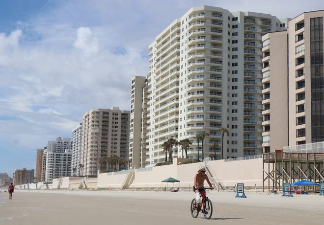 A bicyclist rides the beach, Wednesday June 30, 2021 with some of Daytona Beach Shores iconic condominiums in the background.