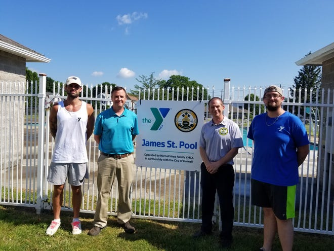 Representatives of the Hornell Family YMCA: aquatics director Seth Gill, CEO Kristoph Kocan, Hornell mayor John Buckley and YMCA Associate Executive Director Nick Kowtun stand beside a sign marking the city's new partnership with the YMCA.