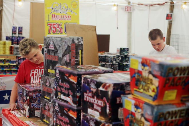 Clayton Milder, 6, and his brother, Victor, 8, of Waterloo, check out the selection of fireworks for sale Tuesday at the Bellino Fireworks tent located in the Burlington Fareway grocery store parking lot.