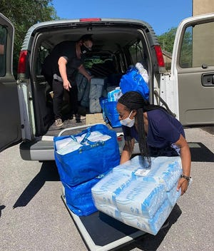 Crystal Parks (foreground), founder and president of the Diaper Bank for Northeast Florida, loads diapers to be distributed to nonprofit partners for families.