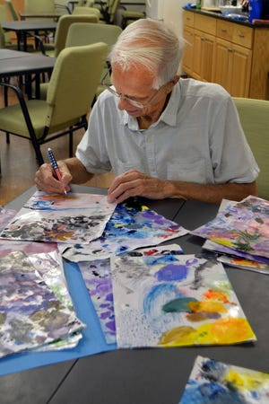 Artist Paul Bisbee Sr. of Baldwinville signs autographs at the recent opening of his art exhibit at the Templeton Senior Community Center.