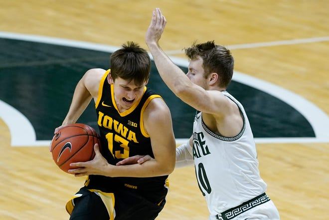 Iowa guard Austin Ash (13) drives on Michigan State guard Jack Hoiberg (10) in the second half of a game in East Lansing, Mich. on Saturday, Feb. 13, 2021.