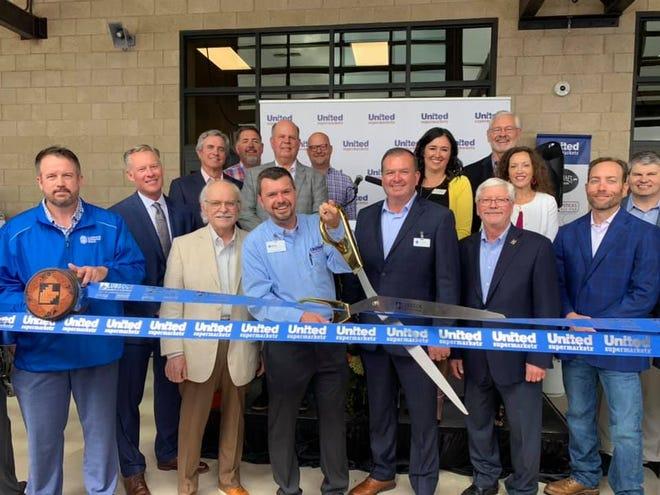 United Supermarkets, 11310 Slide Road. Holding scissors is Eric Steinfath, store director. Holding ribbon are Chamber Ambassadors Bruce Larson, left, and Carmen Vige.