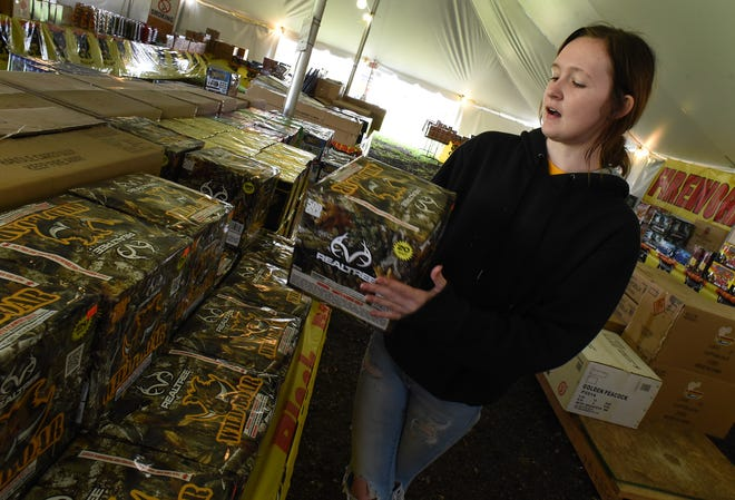 Haily Williams of Woodhaven holds up a package of fireworks for sale inside the Mega Fireworks tent located at the corner of Laplaisance and Albain Roads in Monroe Township.