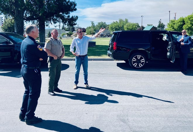 Cal Fire director Thomas Porter, left, and California Gov. Gavin Newsom gaze into the distance at Mt. Shasta from Weed High School on June 29, 2021. Newsom was in Weed to tour the Lava Fire burning near the town.