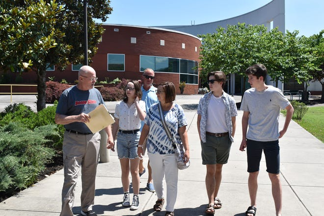 Roane State Community College's Jack Parker talks with the Dunsmore family during their tour of the Coffey/McNally Building,   in background, and the Goff Building on the Oak Ridge Branch Campus. From left are Jack Parker with Megan, Todd and Jennifer Dunsmore, Jacob and Luke.