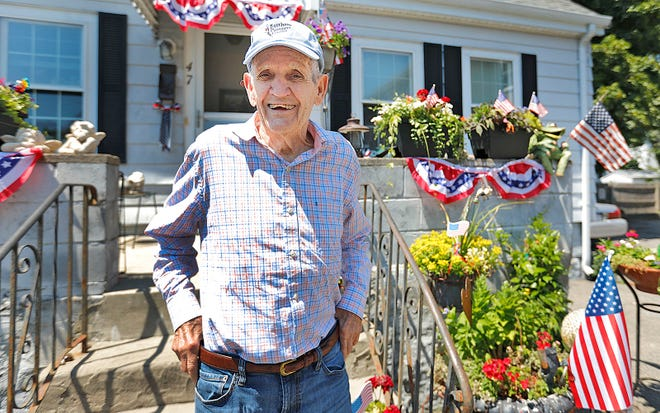 """Quincy veteran Robert Bylaska in front of his Water Street home, which his daughter Sandra decked out for the Fourth of July holiday. Bylaska has memory loss and doesn't remember much about his service in both the Navy and Army, but his daughter says he remains a """"great patriot."""""""