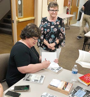 Steidinger signs a copy of her book for Joan Smeltzer at Dominy Library.