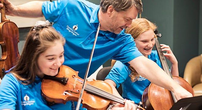 Dorothy Gerber Strings Program music director David Reimer (center)  instructs a group of students.