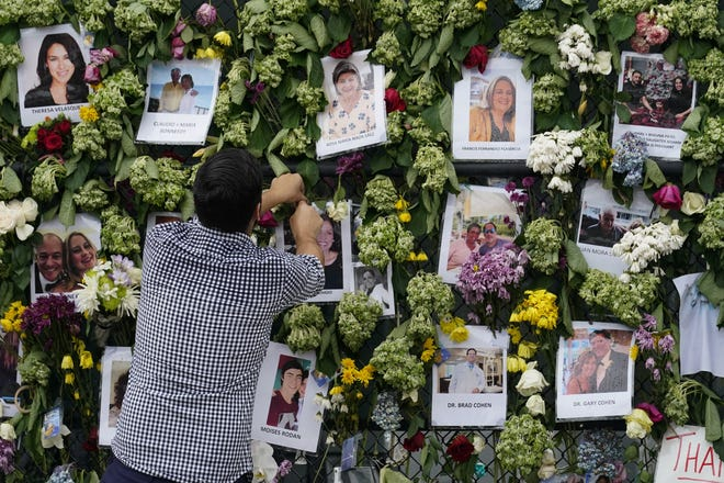Leo Soto, whose high school friend Nicole Langesfeld is missing, along with her husband Luis Sadovnic, adjusts pictures at the makeshift memorial he began to the scores of people who were left missing after the Champlain Towers South condo building partially collapsed.