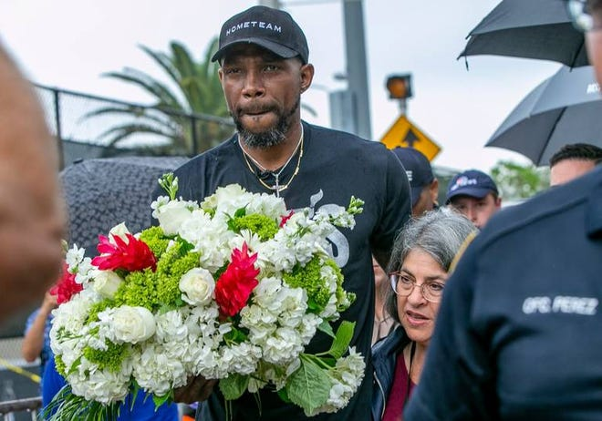 The Miami Heat's Udonis Haslem, left, and Miami-Dade County Mayor Daniella Levine Cava, right, visited the memorial wall for the missing people in the collapsed Champlain Towers South Condo on Wednesday.