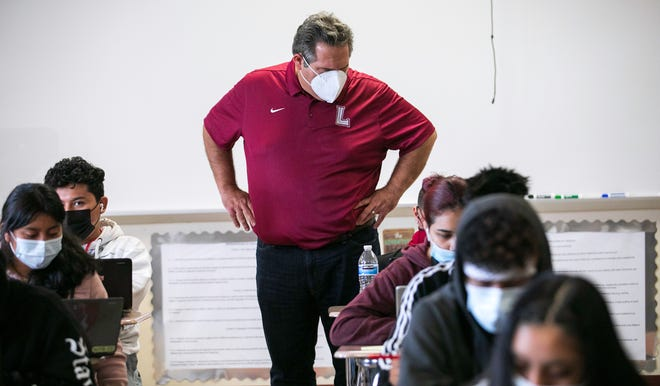 Palm Beach Lakes High School Principal David Alfonso looks over a student's shoulder during summer school Wednesday.