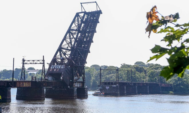 A fire boat travels near the Crook Point Bascule Bridge, which was still smoldering Wednesday morning.