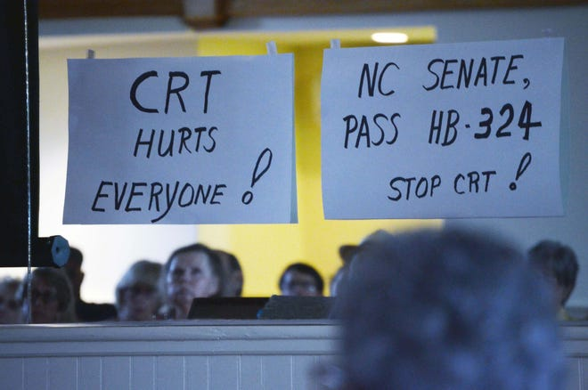 Signs register opposition to the teaching of critical race theory during a recent meeting of the Coastal Carolina Taxpayers Association at Stanly Hall in New Bern. [TODD WETHERINGTON / SUN JOURNAL STAFF]