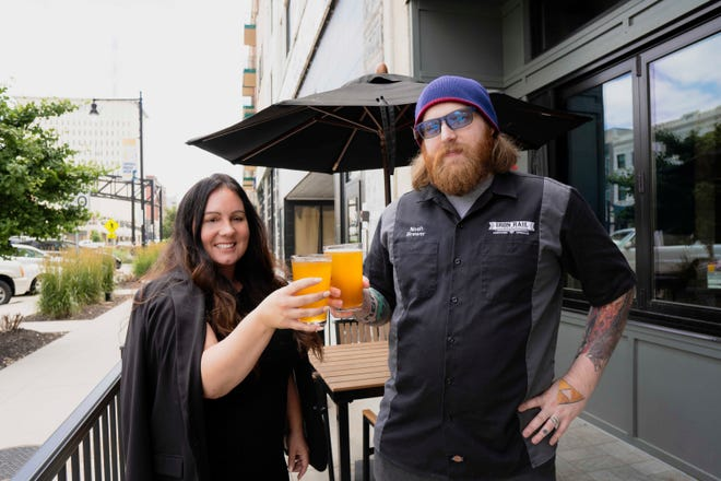 Melissa Jarboe, founder and CEO of Military Veteran Project, and Noah Oswald, Iron Rail Brewing Co. brewmaster, stand outside the restaurant with the Cyrus K. Holliday beer.