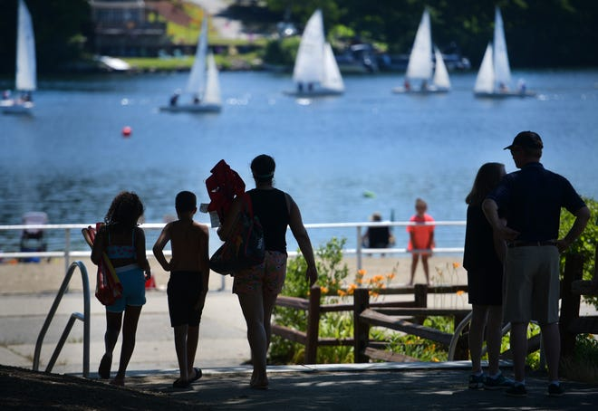 People walk through the shade at Regatta Point to get to the beach in search of relief from the heat Wednesday, as sailboats cruise by under full sail on Lake Quinsigamond in Worcester.