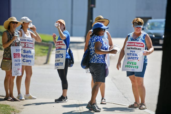 St. Vincent Hospital nurses hydrate near an entrance on Bridge Street in Worcester while picketing during Wednesday's heat wave.