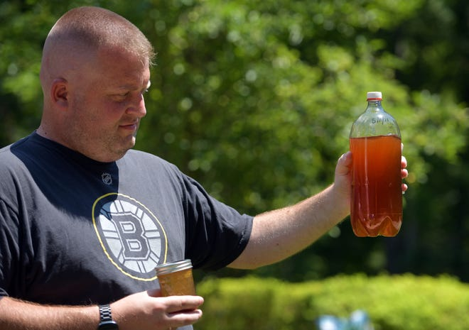 Christopher Buck of the Jefferson section of Holden holds a water sample taken from his home.