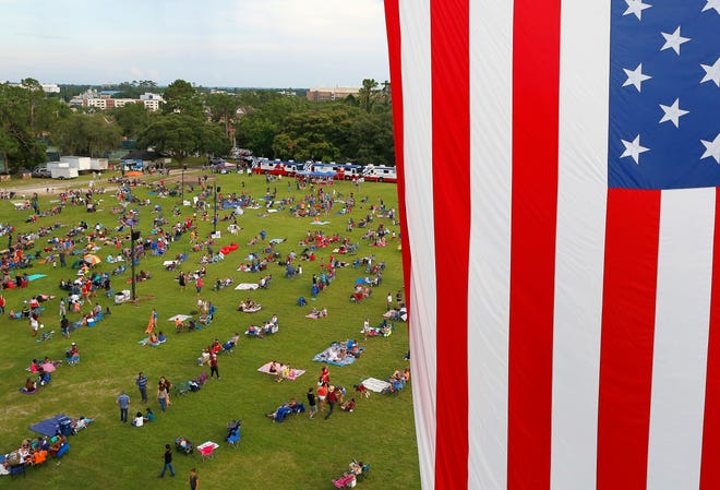 A huge American flag waves over the people enjoying the annual Fanfare and Fireworks celebration of Independence Day held at Flavet Field on the University of Florida campus in 2018.