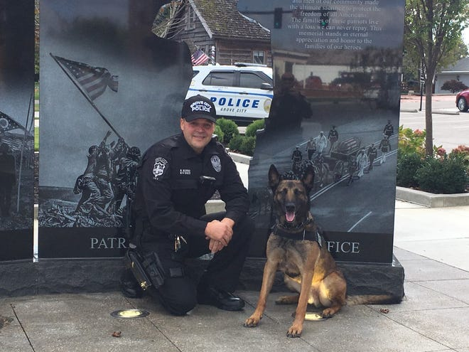 Grove City Division of Police officer Brian Kitko and K-9 officer Max pose for a photo in front of a memorial. Max died of cancer during surgery June 9.