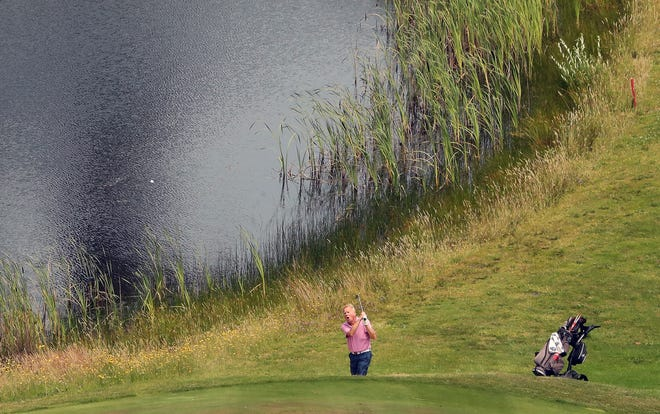 A golfer chips a shot onto the 18th green on the Olympic Course at Gold Mountain Golf Club on Wednesday, June 30, 2021. Gold Mountain is hosting the state Men's Amateur Championship beginning Tuesday.